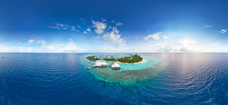Aerial panorama of tropical paradise white sand beach with Turquoise ocean and small bungalows between coconut palm trees in the Maldives.