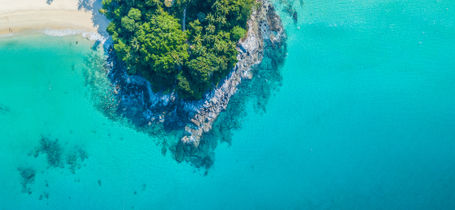 Aerial drone view of rocky outcrop with white sand beach and turquoise clear water with shall reef in Phuket, Thailand.