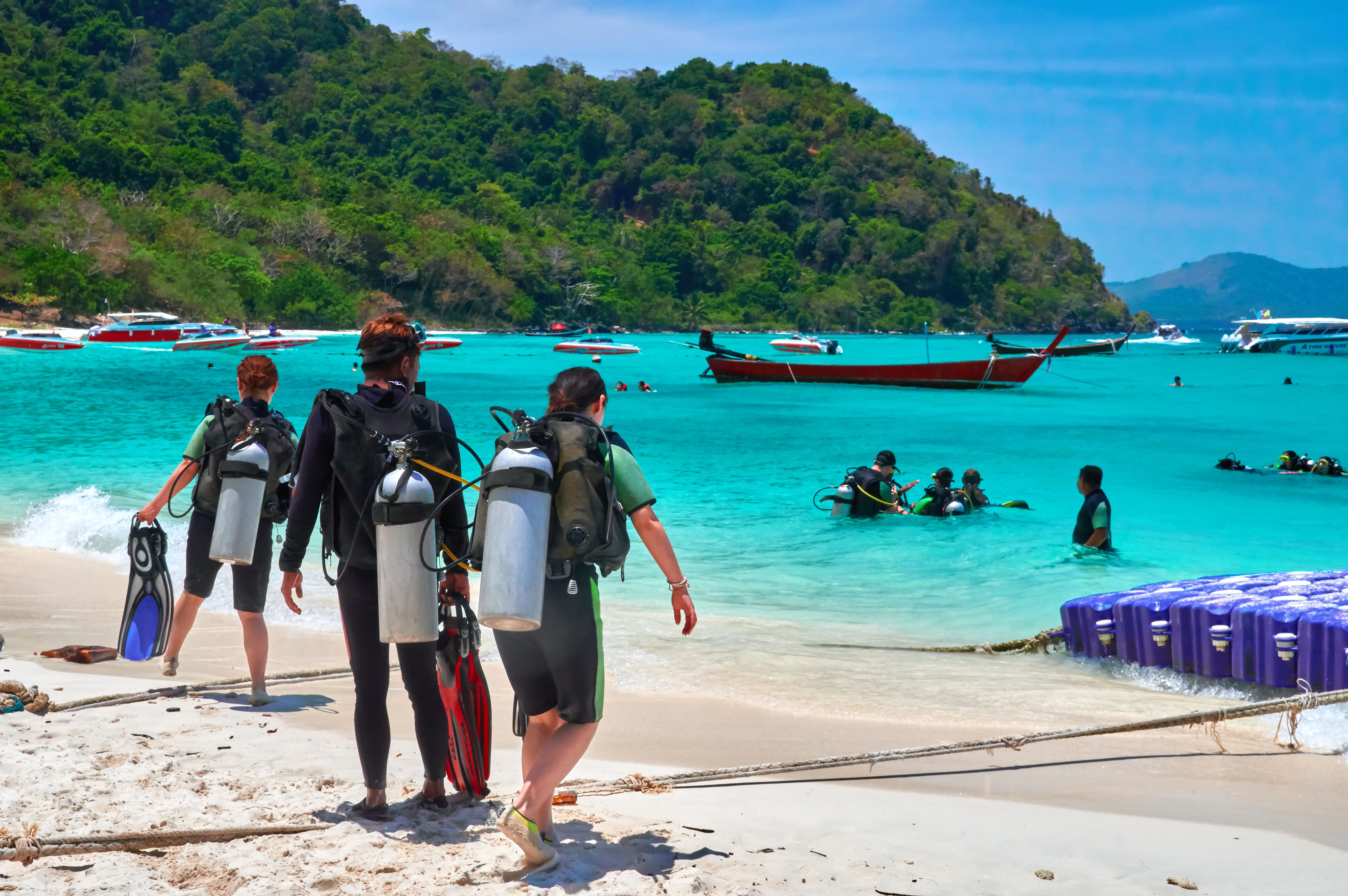 Scuba divers on white sand beach walking towards turquoise bay with divers learning to dive in shallow water.