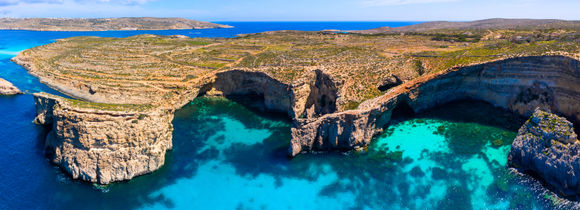 Aerial drone view of Comino Island caves next to crystal clear turquoise waters in Malta