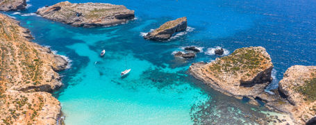 Aerial view of the clear turquoise waters and rocky outcrops of Blue Lagoon on Comino Island in Malta