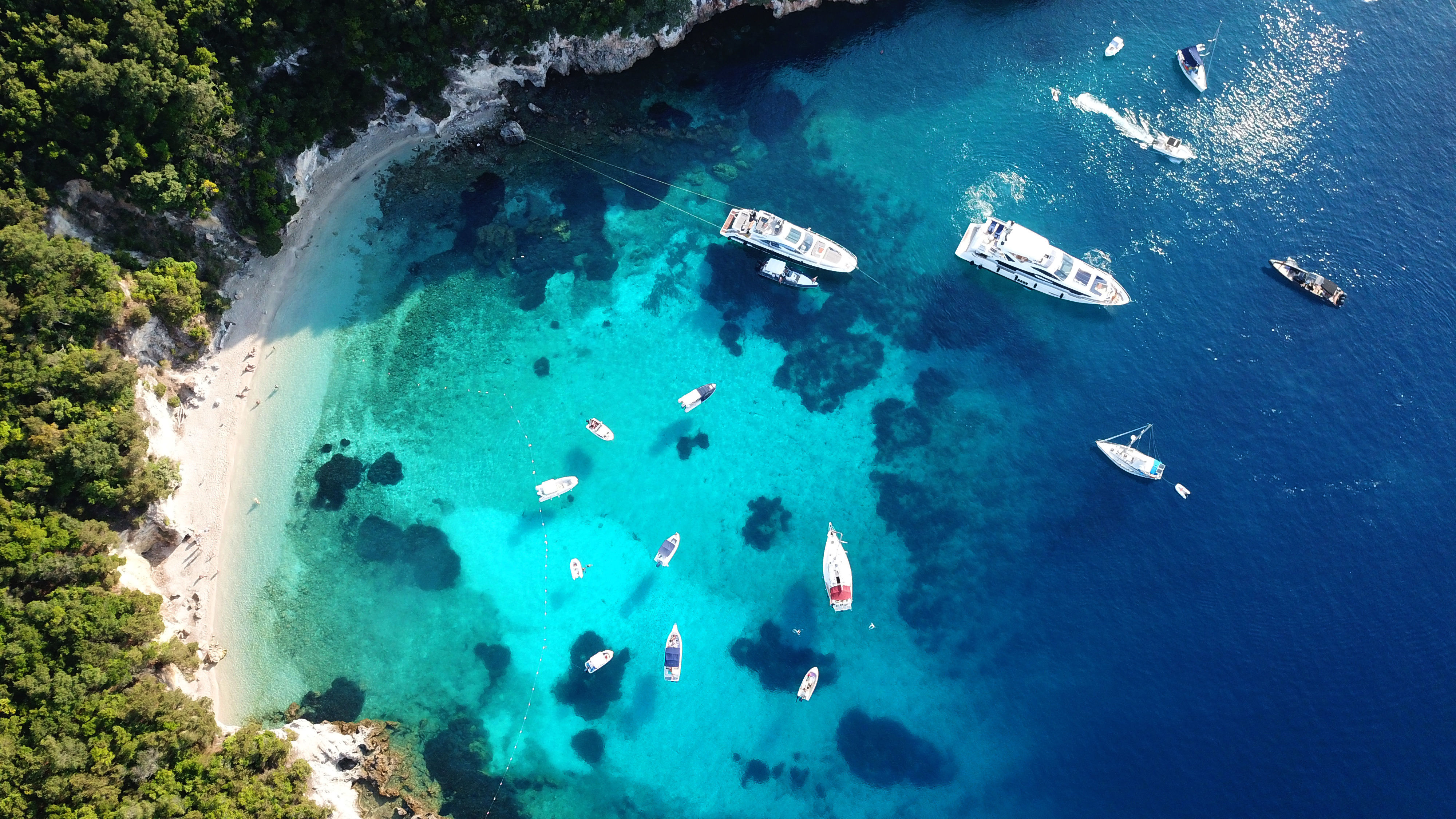 Aerial drone view photo of sail boats in tropical caribbean turquoise clear paradise bay with white rock caves in Cayman Islands.