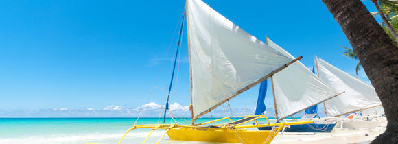 Colorful traditional Filipino boats on white sand shore, near crystal clear turquoise water in Visayas.