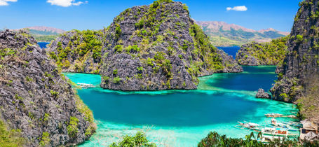Limestone Islands surrounded by clear blue and turquoise waters and moored Filipino boats in Palawan.