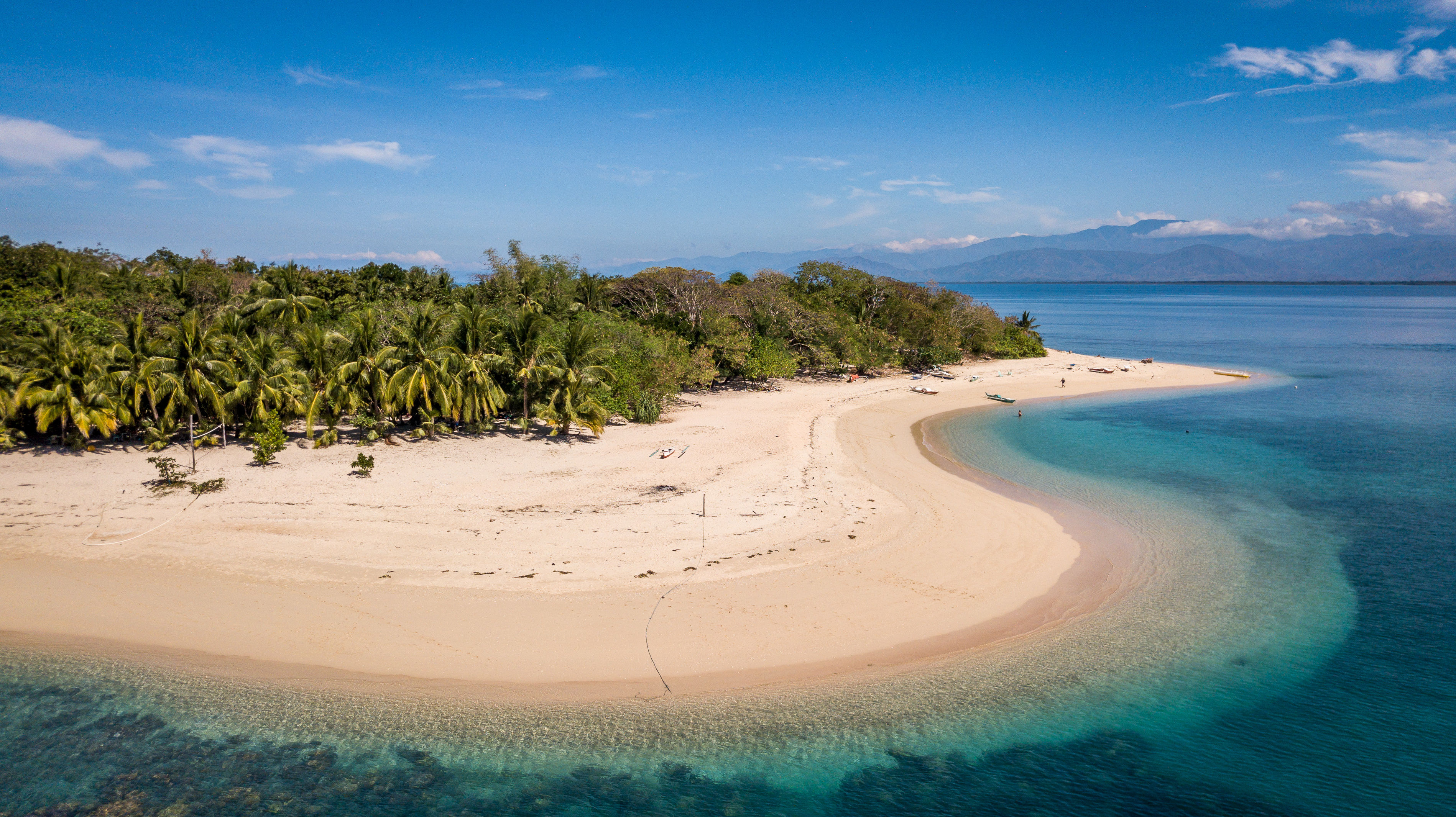 Aerial view of white sand tropical island of Mindoro with green palm trees and surrounded by clear turquoise waters, Philippines.