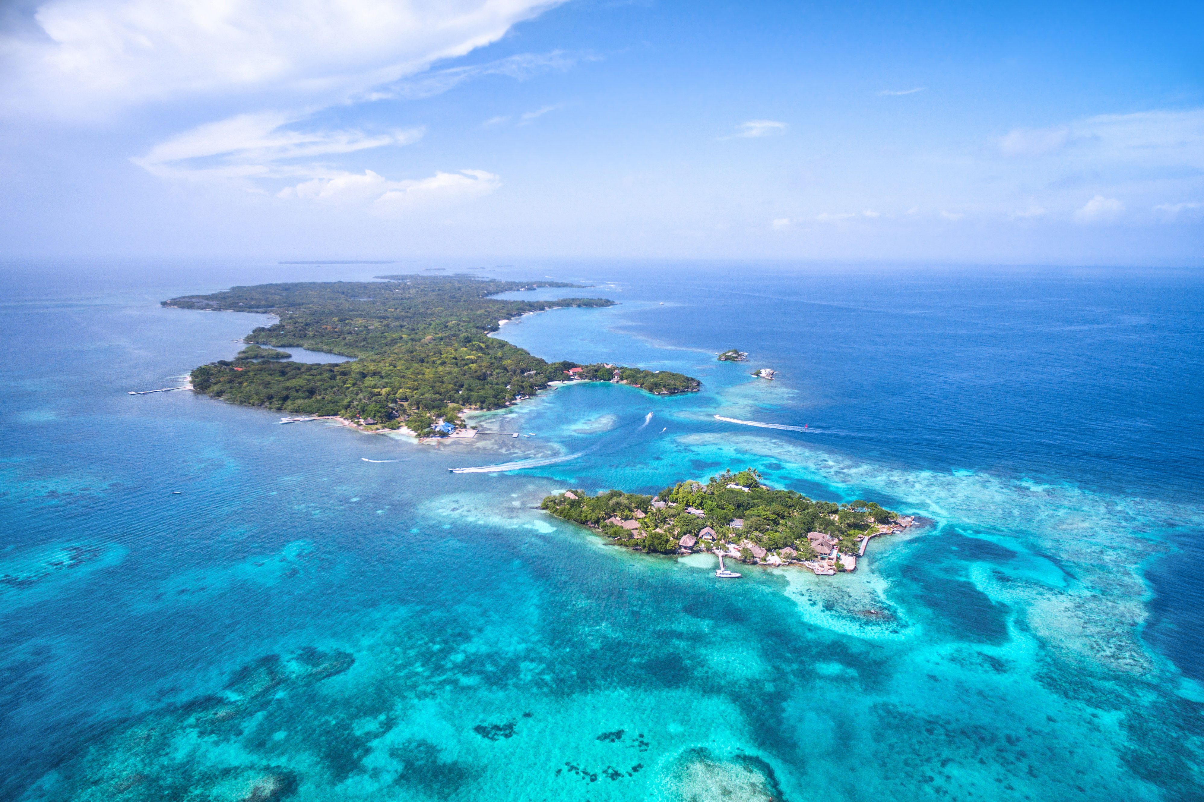 Aerial view of lush green Rosario Islands in Colombia surrounded by tropical turquoise clear waters.