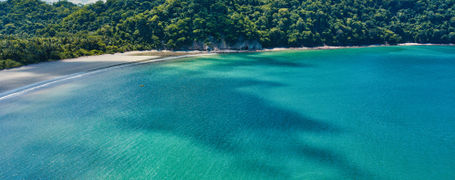 An empty, beautiful white sand beach around the Gulf of Nicoya in Costa Rica with lush green hills and turquoise waters.