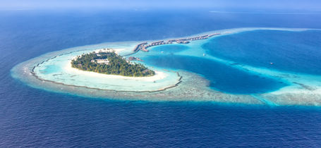 Aerial drone view of Maldivian Ari Atoll with white sand and turquoise waters.