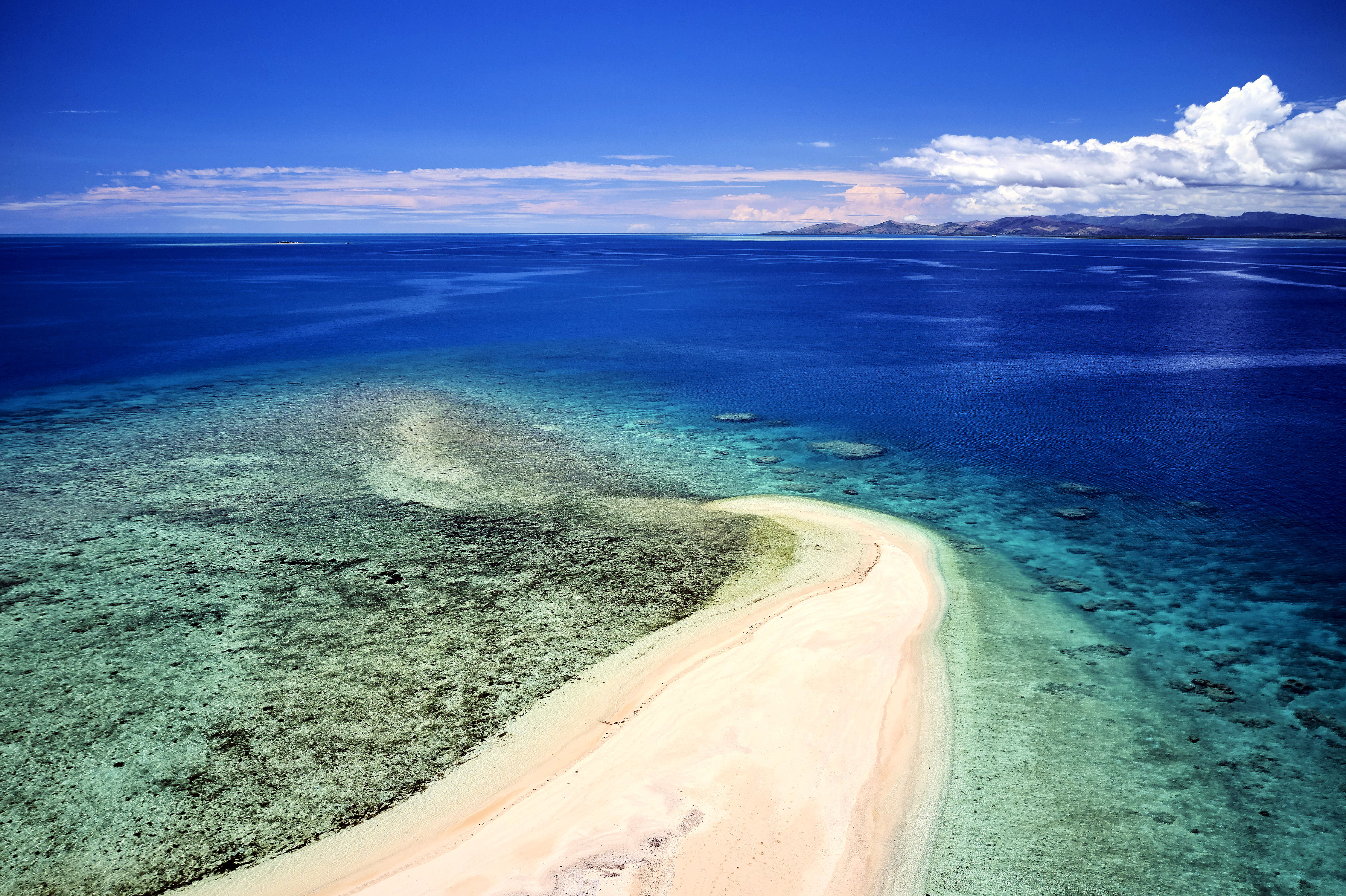 Aerial view of remote island in Fiji overlooking blue coral reef